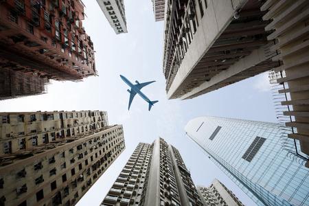 背の高い都市建物、頭上を飛ぶ飛行機