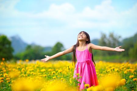 Open arms asian little girl in beautiful flower spring meadow