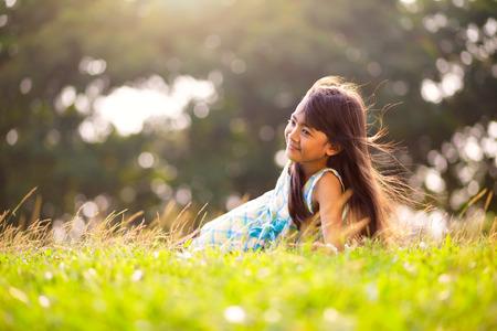 日当たりの良い夏の日、屋外の肖像画に草に敷設小さなかわいいアジアの女の子 写真素材