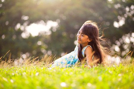 Cute little asian girl laying in the grass on a sunny summer day, Outdoor portrait Фото со стока - 39248889