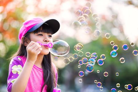 burbujas de jabon: La niña encantadora soplando pompas de jabón asiático, retrato al aire libre