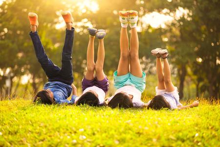 enfant qui joue: Groupe d'enfants heureux couch� sur l'herbe verte en plein air dans le parc de printemps