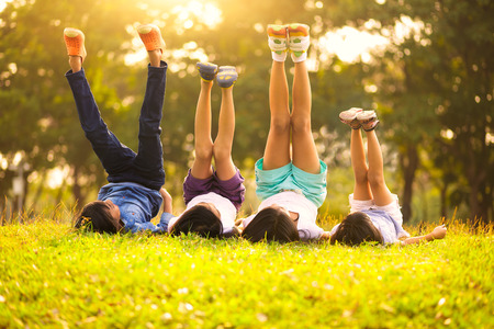 ni�os jugando: Grupo de ni�os felices acostado en la hierba verde al aire libre en el parque de la primavera Foto de archivo