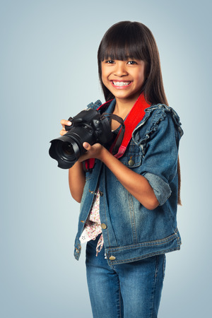cross process: Smiling young asian girl holding photo camera, Cross process Color Tone