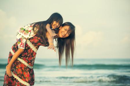 幸せな母、ビーチで彼女の娘を保持クロス プロセス色のトーン