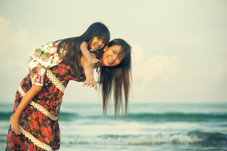 cross process: Happy mother holding her daughter on the beach, Cross process Color tone