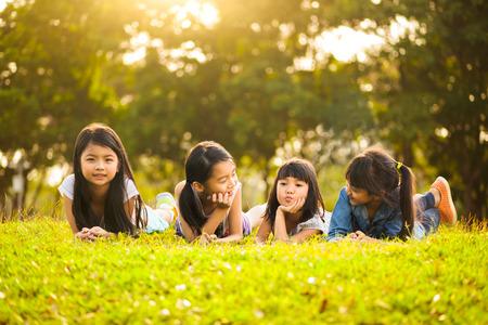 familia feliz: Las ni�as asi�ticas que ponen en la hierba verde bajo la luz del sol