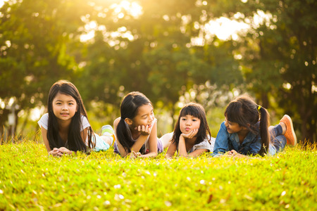 sunbeam: Little asian girls laying on the green grass under sunlight