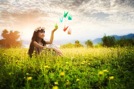 mujer sentada: Niña linda que se sienta en el césped en el parque con grullas de origami, retrato al aire libre