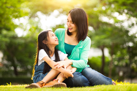 asian child: Happy young mother with her daughter at park Stock Photo