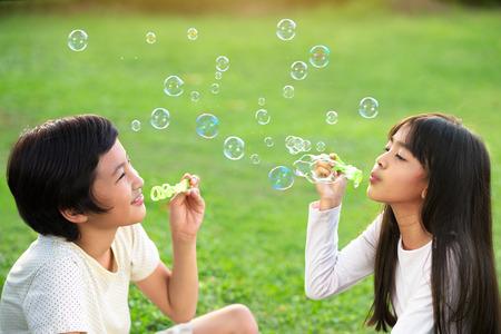 burbujas de jabon: Los niños en el parque soplando pompas de jabón Foto de archivo