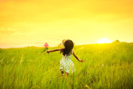 Little girl running on meadow with sunset 스톡 콘텐츠