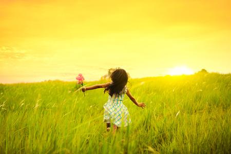 mujeres y niños: Niña que se ejecuta en prado con la puesta de sol