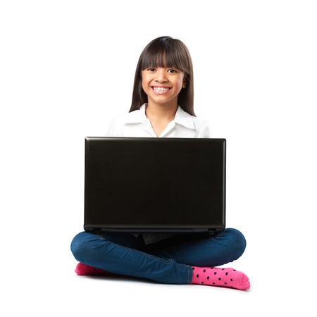 Little asian girl sitting on a floor with her laptop Isolated over white photo