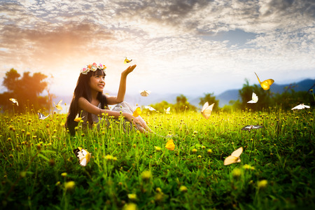 butterfly in hand: Little asian girl in garden with hands up and butterflys Stock Photo