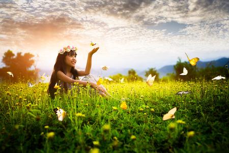 felicidad: Niña asiática en el jardín con las manos arriba y mariposas