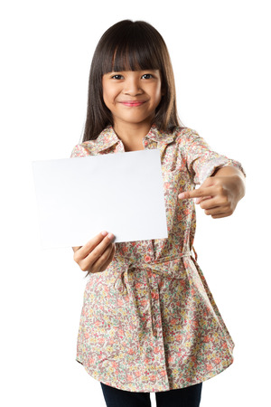 Smiling little asian girl holding an empty white paper for you sample text, Isolated over white