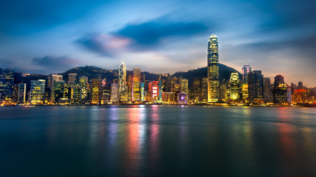hong kong: Hong kong city skyline at night over victoria harbor with clear sky and urban skyscrapers
