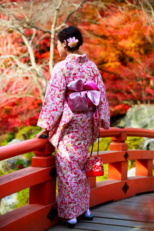 Rear view of japanese girl in a kimono standing in the gardens Фото со стока