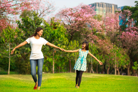 asia children: Happy family mother and child little daughter running and playing at park