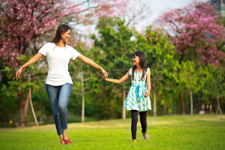 ni�os jugando en el parque: Feliz madre de familia y del ni�o peque�o hija corriendo y jugando en el parque
