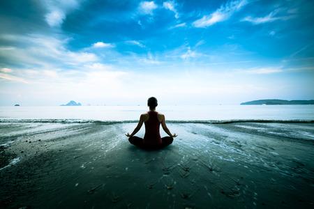 Mujer joven silueta practicando yoga en la playa