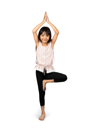 little girl smiling: Little asian girl doing yoga exercises Isolated over white Stock Photo