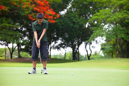 teen golf: Hombre joven que mira después de que el putt que acaba de formular