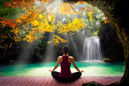 Young woman in yoga pose sitting near watefall Rear view Stockfoto