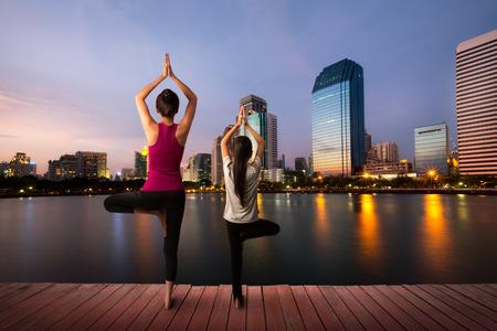 Mère et fille faisant du yoga à la ville