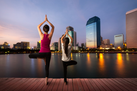 outdoor fitness: Mother and daughter doing yoga at city