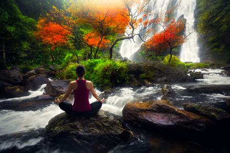 waterfalls: Young woman in yoga pose sitting near watefall, Rear view