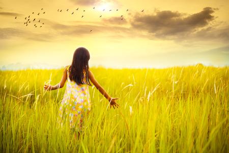夕焼けの草原の上を歩く少女 写真素材