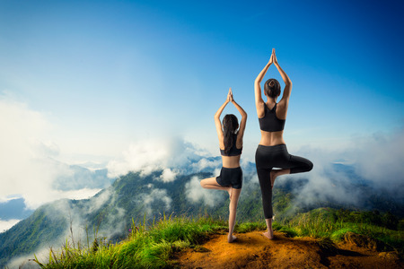 teaching adult: Mother and daughter doing yoga at top of mountain Stock Photo