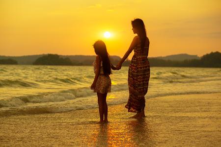 母と娘の夜明け時ビーチに歩いています。