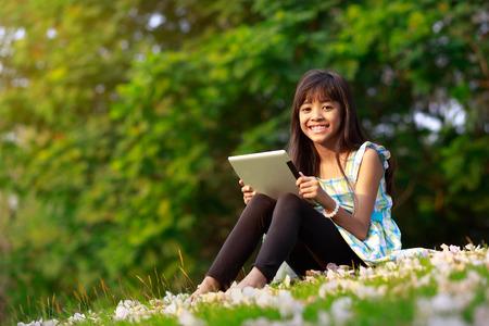 niños jugando en el parque: Muchacha asiática feliz sentado en la hierba con tablet PC en el parque Foto de archivo