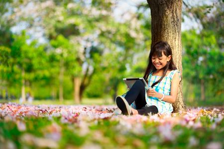 niñas jugando: Muchacha asiática feliz sentado en la hierba con tablet PC en el parque Foto de archivo