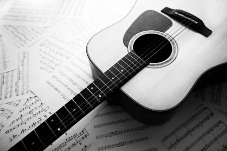 gutar: Acoustic guitar laying across sheet music, Black  White tone