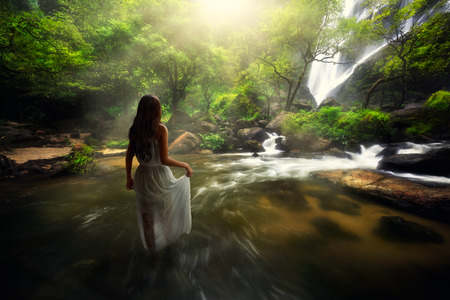 Young asian woman standing by a stream in the forest