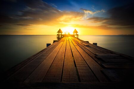 horizon over water: Wooded bridge at sunset Stock Photo