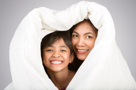 convivencia familiar: Hija y madre son felices juntos bajo las sábanas en el dormitorio