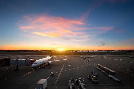 夕暮れ時、空港のターミナルのそばの飛行機