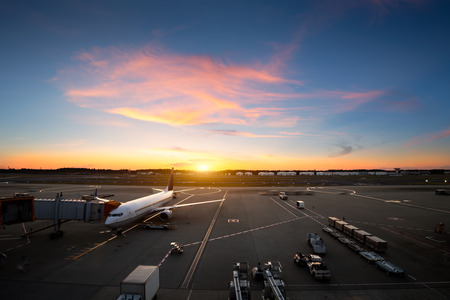 Airplane near the terminal in an airport at the sunset Foto de archivo