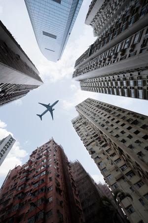 航空機: 背の高いビルと頭上を飛ぶ飛行機
