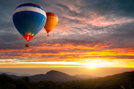 sunset clouds: Colorful hot-air balloons flying over the mountain Stock Photo