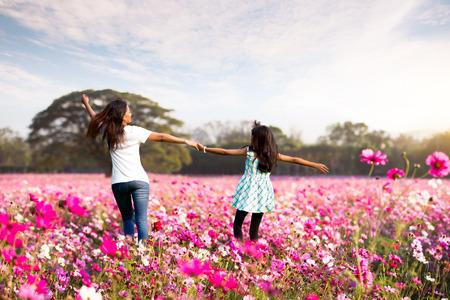 幸せな家族の母と子の少女再生と草原の上を実行している小さな娘