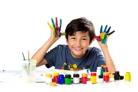 niño escuela: Muchacho asiático joven con las manos en la pintura, aislado en blanco Foto de archivo