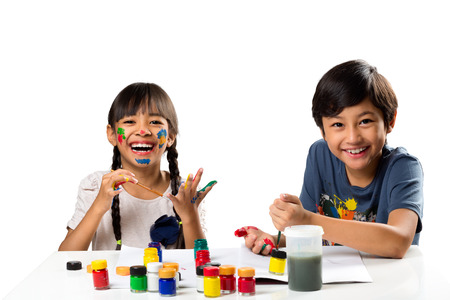 Two smiling little kids at the table draw with water color, Isolated over white Stock Photo