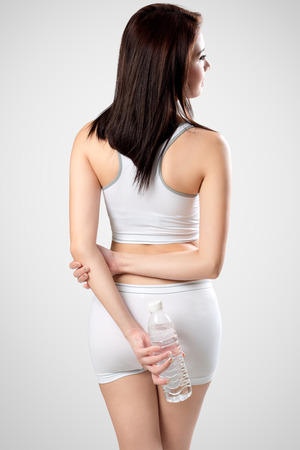 view woman: Rear view of sporty woman with water bottle, Isolated on grey background