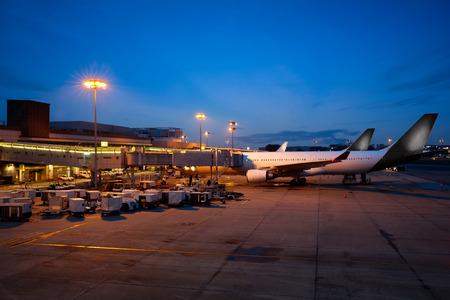Vliegtuig in de buurt van de terminal in een luchthaven in de schemering, de internationale luchthaven Changi